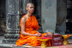 Monk. SIEM REAP, CAMBODIA - 26 May 2017, A young monk sits in the temple complex of Angkor Wat. For a little donation he will pray for your goodluck stock image