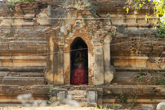 Sitting in Ancient Prayer. A monk sits in an ancient temple in prayer in Hanlin, Myanmar Royalty Free Stock Photo