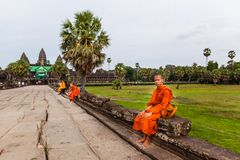 Monk sits on causeway of Angkor Wat Temple Royalty Free Stock Photo