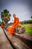 Monk sits on causeway of Angkor Wat Temple Royalty Free Stock Image