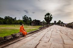 Monk sits on causeway of Angkor Wat Temple Royalty Free Stock Photography