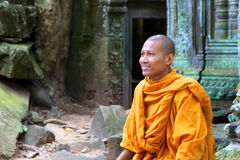 A monk sits on ruins of the Ta Phrom temple Royalty Free Stock Photo
