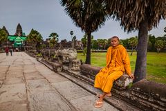 Monk sits on walkway of Angkor Wat Temple Royalty Free Stock Photos