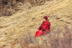 Monk sitting praying on grasses in the mountain at Larung GarLarung Buddhist Academy royalty free stock images