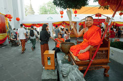 Monk sprinkles holy water temple visitors inside famous monastery Wat Pho stock photos