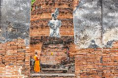 Monk standing in praying in front of buddha statue at old temple, Ayutthaya Province Royalty Free Stock Photography