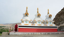 A monk standing beside White stupas at Thikse temple in Ladakh, India Stock Images