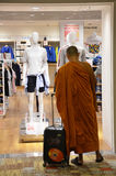 Monk stands in front of the Uniqlo store in Changi Airport Royalty Free Stock Image