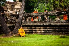 Monk stands on moat wall at Angkor Wat Temple Royalty Free Stock Photography