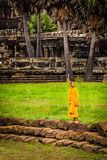 Monk stands on moat wall at Angkor Wat Temple Stock Image