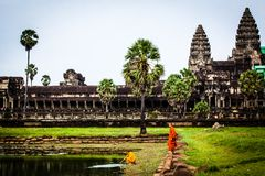 Monk stands on moat wall at Angkor Wat Temple Royalty Free Stock Photo