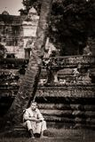 Monk stands on moat wall at Angkor Wat Temple Stock Photography
