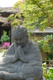 Monk statue under tree China. One grey monk statue put palms together. Covered by shadows of the green tree Royalty Free Stock Image