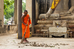 Monk sweeping leaf in front of statue buddhist Stock Photos