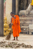Monk sweeping leaf in front of statue buddhist Stock Image