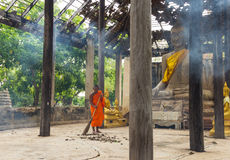 Monk sweeping leaf in the old chapel Royalty Free Stock Photos