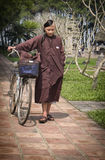 Monk in Traininig, Hue, Vietnam. A boy training to be a monk, noted by his hair which is only half shaven,  walks his bike in Hue, central Vietnam Stock Image