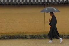 Monk with umbrella. Japanese Buddhist monk at Horyuji carrying an umbrella in the rain royalty free stock photos