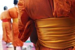 Monk walking. Detail of orange dress of monk during praying in buddhist temple Stock Photography