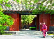 A monk walking inside the lama temple. A Buddhist monk walking to a gate inside Yonghegong Lamasery in Beijing China Stock Image