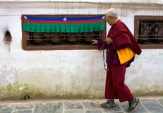 Monk walking prayer wheels Royalty Free Stock Photos
