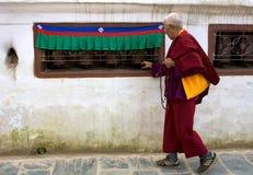 Monk walking prayer wheels Royalty Free Stock Photos