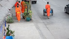 Monk walking on the road for people pray and put food offerings. To Buddhist alms bowl at morning time on Febuary 23, 2015 in Chiangrai, Thailand. Chiang Rai ( stock video