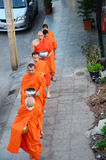 Monk walking on the road for people pray and put food offerings Stock Images
