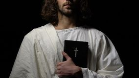 Monk in white robe holding holy bible against dark background, Christianity. Stock footage stock footage