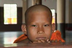 Monk at window. KANCHANABURI, THAILAND - MARCH 11: A youth monk at window on March 11, 2011 in Sangkhlaburi, Kanchanaburi, Thailand. The 100 year anniversary Royalty Free Stock Photos