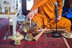 Monken gör helgedom bevattnar slutet av stearinljuset för melten för handen för ` s för den buddistiska munken den hällande river Arkivfoton