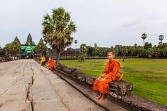 Monken sitter på causewayen av det Angkor Wat tempelet Royaltyfri Foto