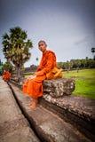Monken sitter på causewayen av det Angkor Wat tempelet Royaltyfri Bild