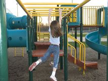Monkey Bars. A young girl does the hanging walk along the monkey bars royalty free stock image