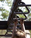 Monkey bars. Child hanging from monkey bars stock images