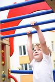Monkey bars. Kid doing chin-ups, his father helping him. do exercises on the crossbar in the park. practice on the bar. Monkey bars. Kid doing exercises on the Stock Image