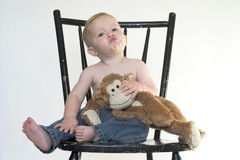 Monkey Boy. Image of a cute toddler sitting on a black chair, holding a stuffed monkey Stock Images