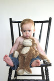 Monkey Boy. Image of a cute toddler sitting on a black chair, holding a stuffed monkey Royalty Free Stock Photography