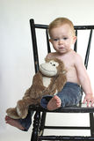 Monkey Boy. Image of a cute toddler sitting on a black chair, holding a stuffed monkey Stock Photos