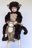 Monkey Boy. Image of cute toddler wearing a monkey costume, holding a stuffed monkey Stock Photo