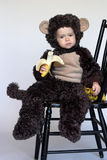 Monkey Boy. Image of cute toddler wearing a monkey costume, eating a banana Royalty Free Stock Photos
