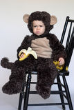 Monkey Boy. Image of cute toddler wearing a monkey costume, eating a banana Royalty Free Stock Photo