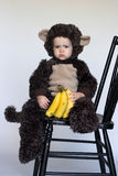 Monkey Boy. Image of cute toddler wearing a monkey costume, holding a bunch of bananas Royalty Free Stock Photo