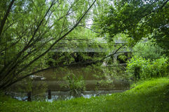 Monkey bridge for pedestrians and bikers next to the river Stock Images