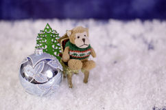 Monkey on a chair. Near Christmas toy ball and herringbone. Stock Photography