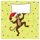 Monkey dans un chapeau rouge jugeant une affiche avec des félicitations heureuse Photos libres de droits