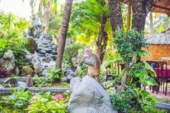The monkey eats a banana in a tropical garden Stock Photo