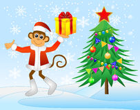 Monkey with gift and decorated Christmas tree Royalty Free Stock Photos