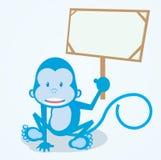 Monkey holding announcement board. Blue monkey sit with holding announcement wooden board Stock Photo