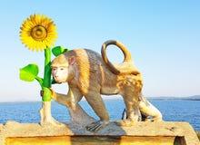 Monkey holding sunflower statue at Pasak Jolasid Dam, Thailand Royalty Free Stock Photo